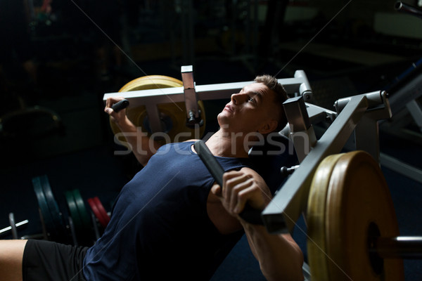 man doing chest press on exercise machine in gym Stock photo © dolgachov