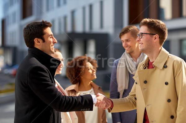 happy people shaking hands on city street Stock photo © dolgachov