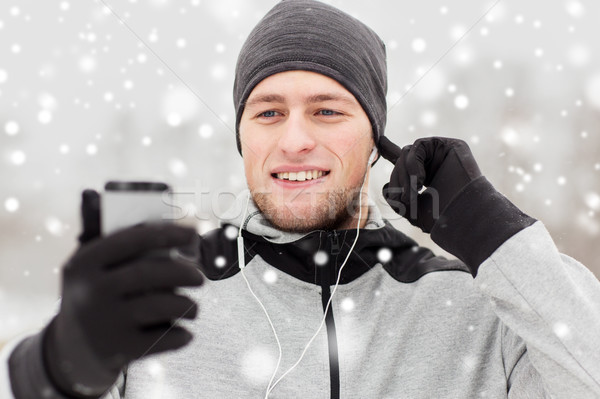 happy man with earphones and smartphone in winter Stock photo © dolgachov