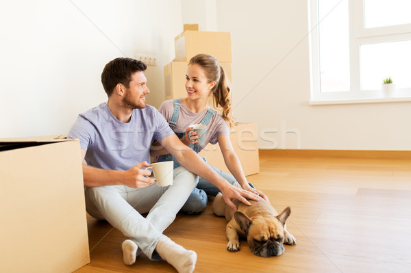 happy couple with boxes and dog moving to new home Stock photo © dolgachov