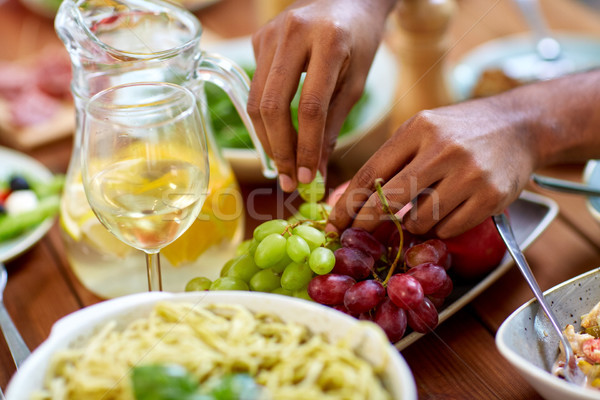 hands taking grape from plate with fruits Stock photo © dolgachov