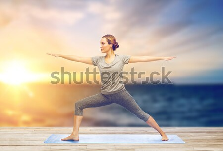 woman making yoga low angle lunge pose on mat Stock photo © dolgachov