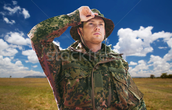 soldier or traveler in military uniform over sky Stock photo © dolgachov