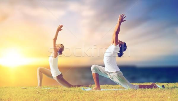 couple making yoga low lunge pose outdoors Stock photo © dolgachov