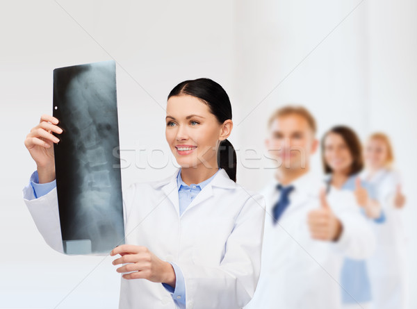 smiling female doctor looking at x-ray Stock photo © dolgachov
