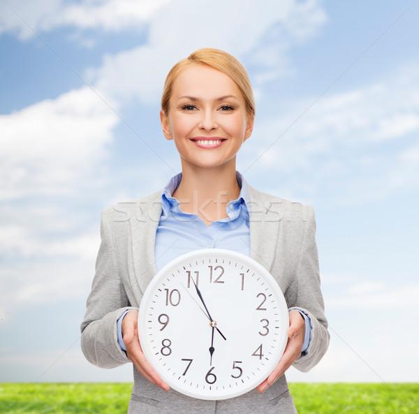 Sorridente empresária parede relógio negócio tempo Foto stock © dolgachov