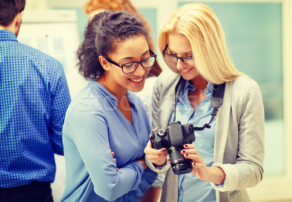two women looking at digital camera at office Stock photo © dolgachov