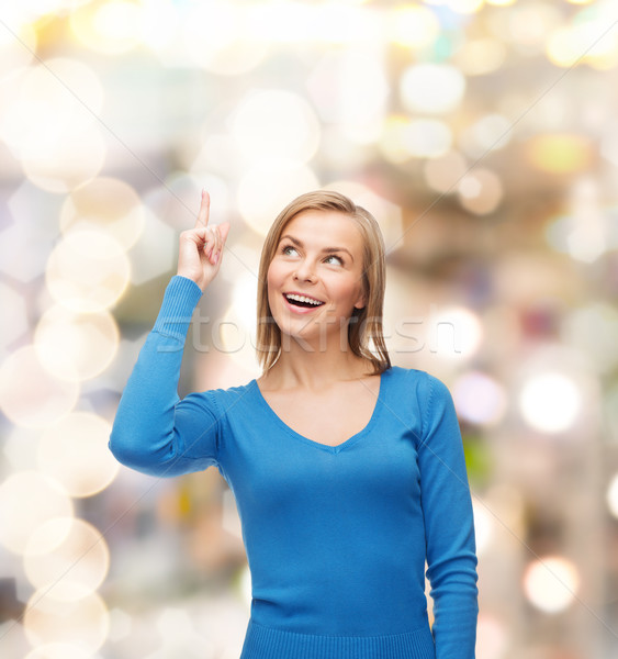 smiling woman pointing her finger up Stock photo © dolgachov