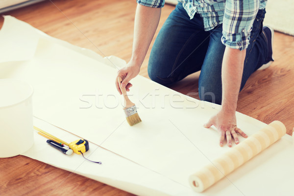 closeup of male hands smearing wallpaper with glue Stock photo © dolgachov