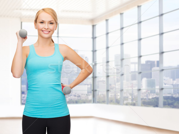 Stock photo: smiling woman with dumbbells flexing biceps in gym