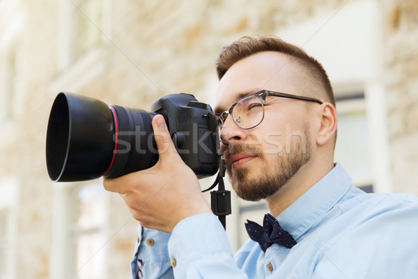 young hipster man with digital camera in city Stock photo © dolgachov