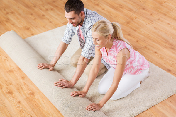 happy couple unrolling carpet or rug at home Stock photo © dolgachov