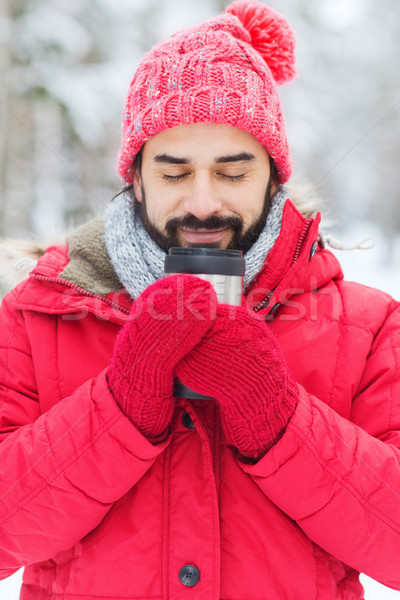 smiling young man with cup in winter forest Stock photo © dolgachov