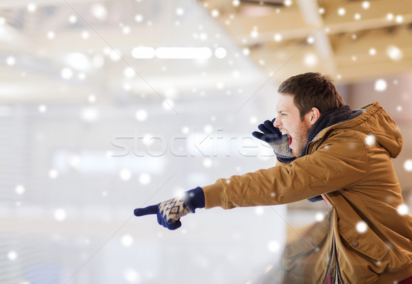 young man supporting hockey game on skating rink Stock photo © dolgachov