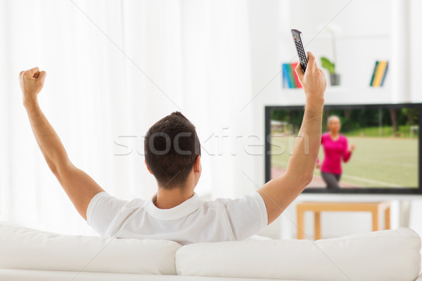 man watching sport channel on tv and at home Stock photo © dolgachov