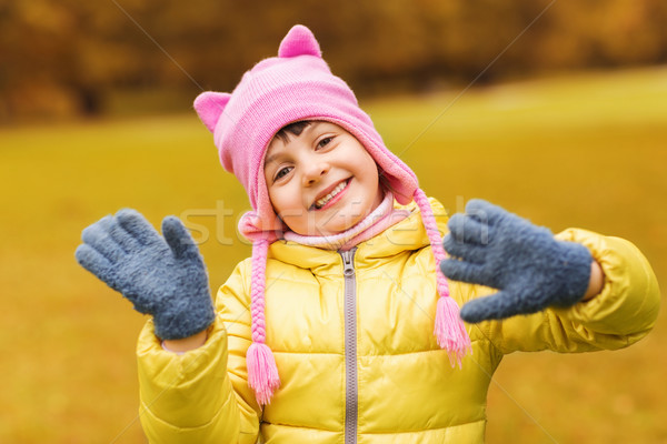 happy beautiful little girl waving hands outdoors Stock photo © dolgachov