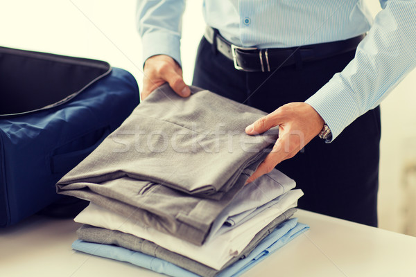 businessman packing clothes into travel bag Stock photo © dolgachov
