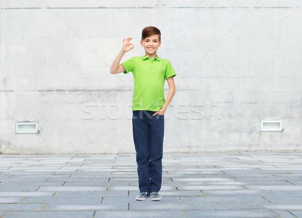 Vidám fiú fehér póló mutat ok kézjel Stock fotó © dolgachov