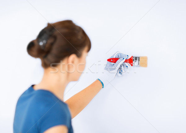 Stock photo: woman with paintbrush colouring the wall