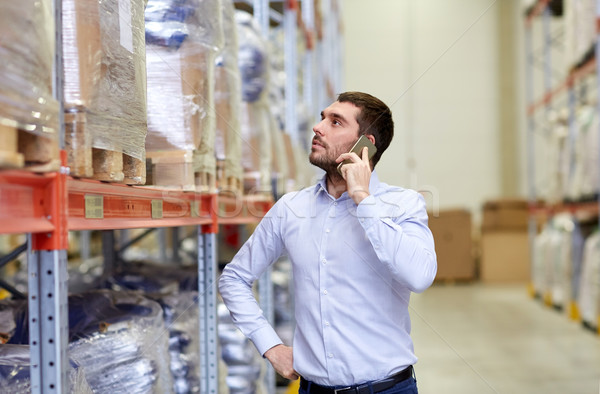 serious man calling on smartphone at warehouse Stock photo © dolgachov
