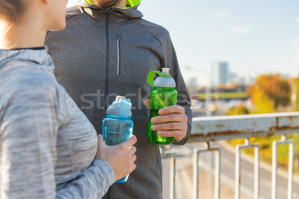 close up of couple with water bottles outdoors Stock photo © dolgachov