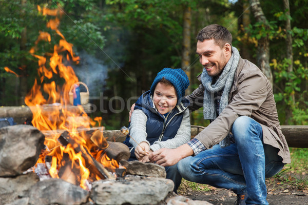 father and son roasting marshmallow over campfire Stock photo © dolgachov