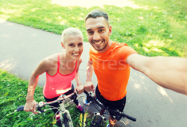 couple with bicycle taking selfie outdoors Stock photo © dolgachov