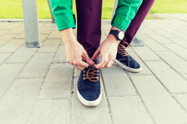 close up of male hands tying shoe laces on street Stock photo © dolgachov