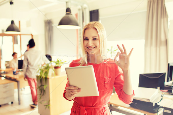 woman with tablet pc showing ok sign at office Stock photo © dolgachov