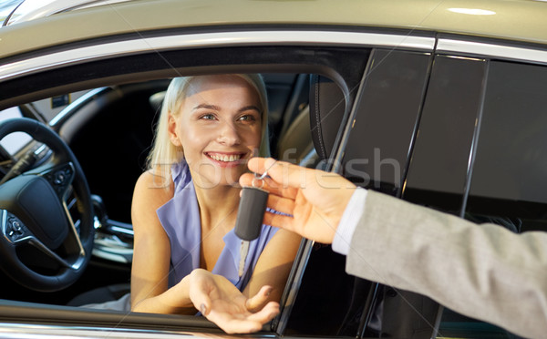 happy woman getting car key in auto show or salon Stock photo © dolgachov