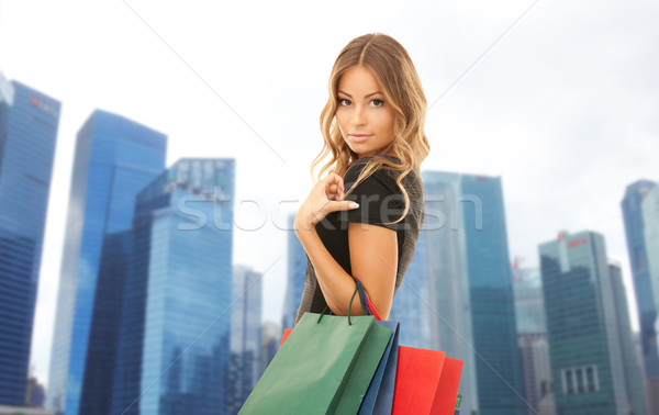 Stock photo: happy woman with shopping bags over singapore city