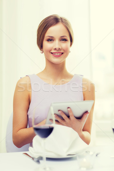 smiling woman with tablet pc computer at resturant Stock photo © dolgachov