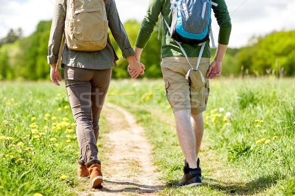 close up of couple with backpacks walking on road Stock photo © dolgachov