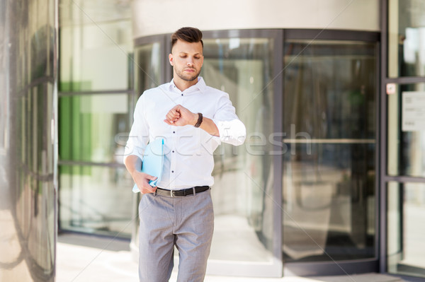 man with folder looking at wristwatch on street Stock photo © dolgachov