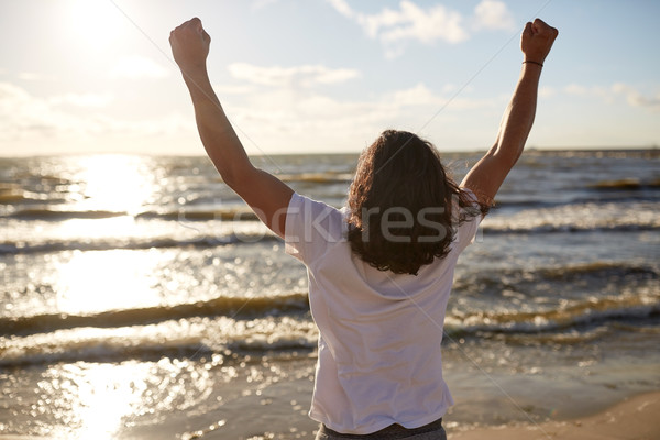 man with rised fist on beach Stock photo © dolgachov