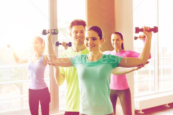 group of smiling people exercising with dumbbells Stock photo © dolgachov
