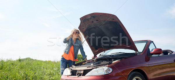 woman with open hood of broken car at countryside Stock photo © dolgachov