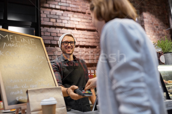 happy woman paying for purchases at cafe Stock photo © dolgachov