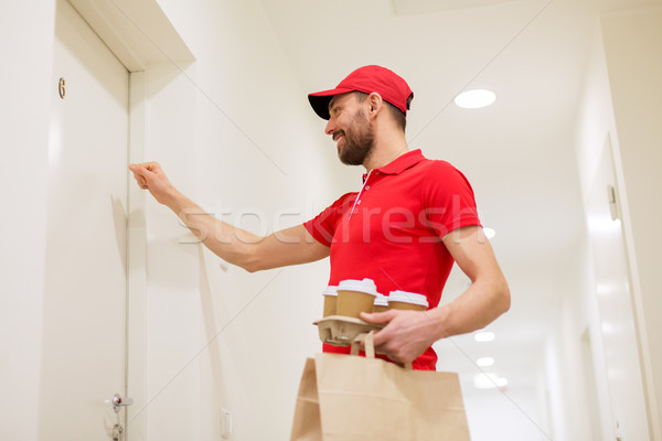 delivery man with coffee and food knocking on door Stock photo © dolgachov