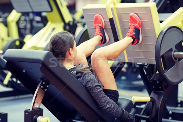 Mujer músculos pierna prensa máquina gimnasio Foto stock © dolgachov