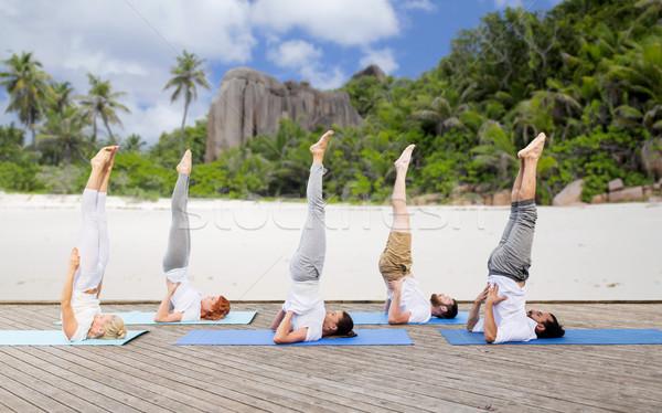 people making yoga in shoulderstand pose on mat Stock photo © dolgachov
