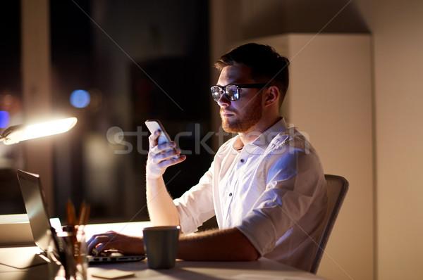 businessman texting on smartphone at night office Stock photo © dolgachov