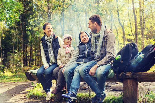 Stock photo: happy family sitting on bench and talking at camp
