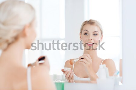Młoda kobieta mleczko kosmetyczne mycia twarz łazienka piękna Zdjęcia stock © dolgachov