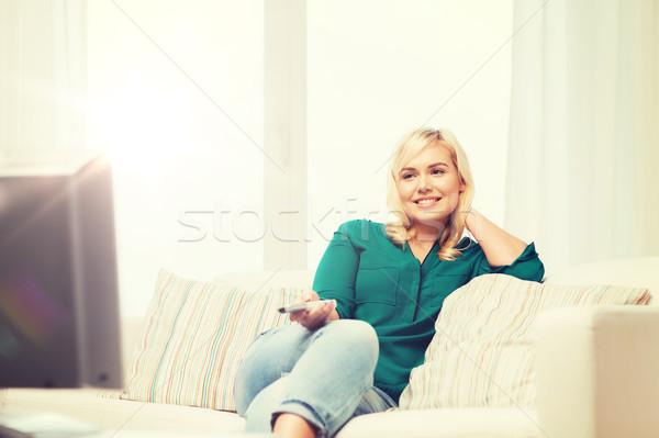 Uśmiechnięta kobieta zdalnego oglądania telewizja domu telewizji Zdjęcia stock © dolgachov