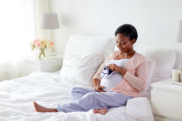 pregnant african woman with baby bootees in bed Stock photo © dolgachov