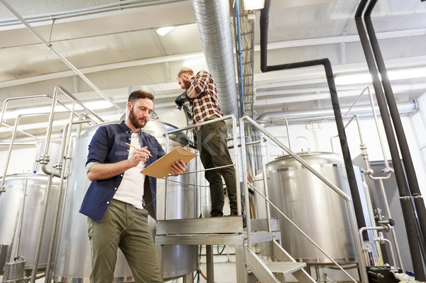 men with clipboard at brewery or beer plant Stock photo © dolgachov