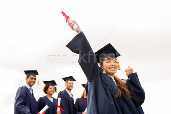 happy students in mortar boards with diplomas Stock photo © dolgachov