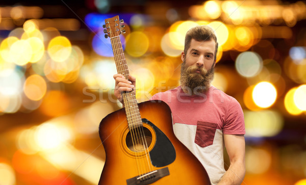 male musician with guitar over night city lights Stock photo © dolgachov