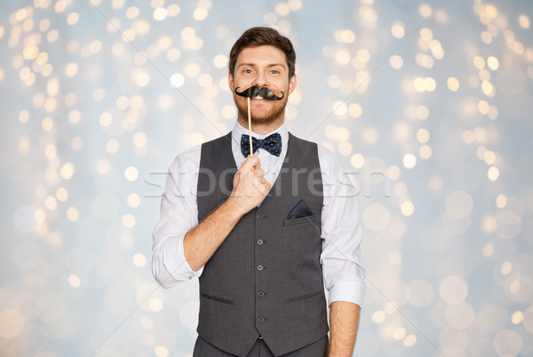 happy young man with fake mustache at party Stock photo © dolgachov